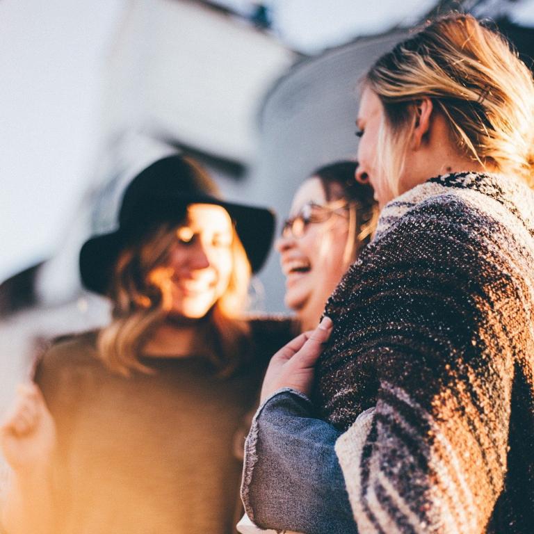 Kolme naista seisoo ulkona keskustelemassa.